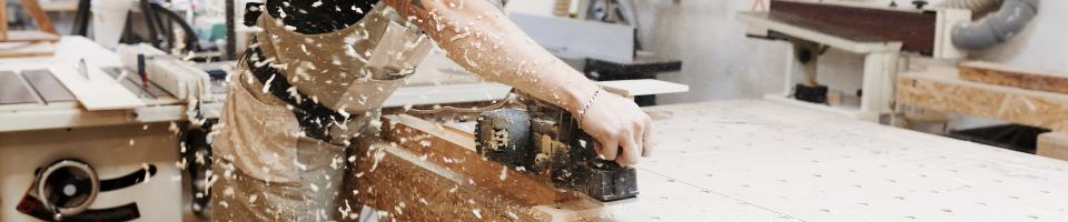 Auszubildender Holzmechaniker bearbeitet Holz mit Hobelmaschine