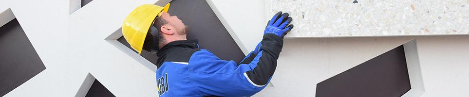 Ein Fassaden-Monteur richtet ein Beton-Fertigteil für die Befestigung aus.
